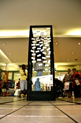 2012, 'Label', Maerua Mall, Windhoek, Namibia.Wechslberger stood in the self-made glass box and provided people andpassers-by, her co-actors, with stickers and markers to label her.
