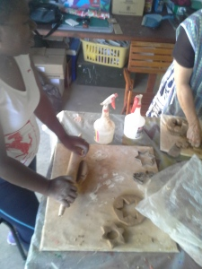 Adults rolling out the clay to make moulds